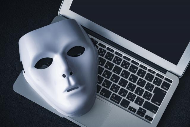 ノートPCの上に置かれた怪しい仮面